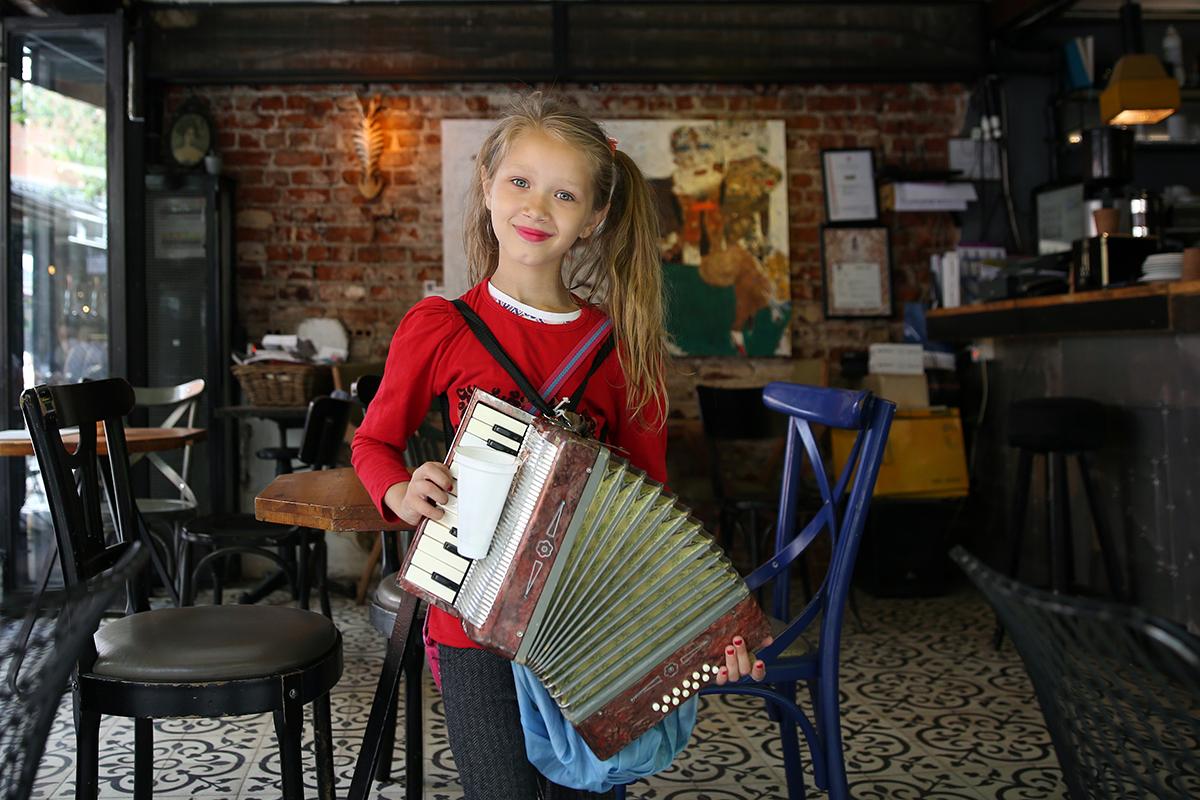 #146 —Karaköy –  Romanian Sera plays accordion amongst the cafés to earn some money.
