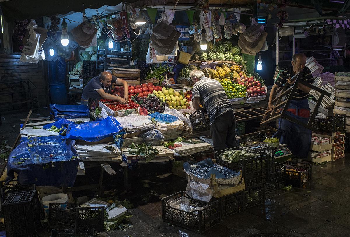 #255 —Kadıköy - Shopkeepers clear their shelves at the day's end at the historical Kadıköy market.